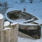 Eingeschneites Holzboot am Strand